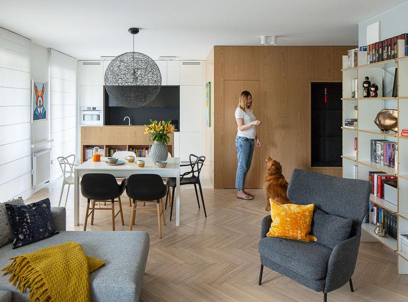 Nowoczesne, przytulne mieszkanie. Drewniana podłoga ułożona w jodełkę. Część ścian została obłożona płytami fornirowanymi.